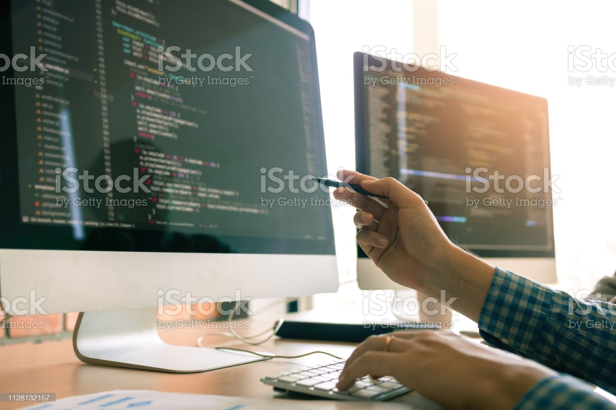 Developing programming working in a software engineers code tech applications on desk in office room.